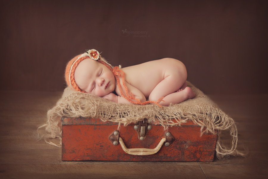 newborn baby girl curled up fast asleep
